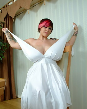 Busty Dors Feline looks alluring in white dress that shows off her miles of cleavage